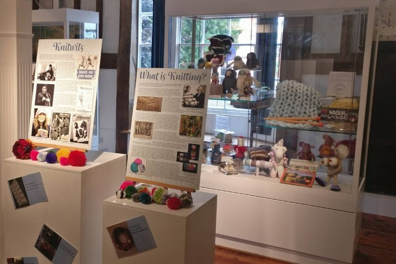 A display of colourful pom poms and knitting materials, part of the 2019 Knitwits exhibition