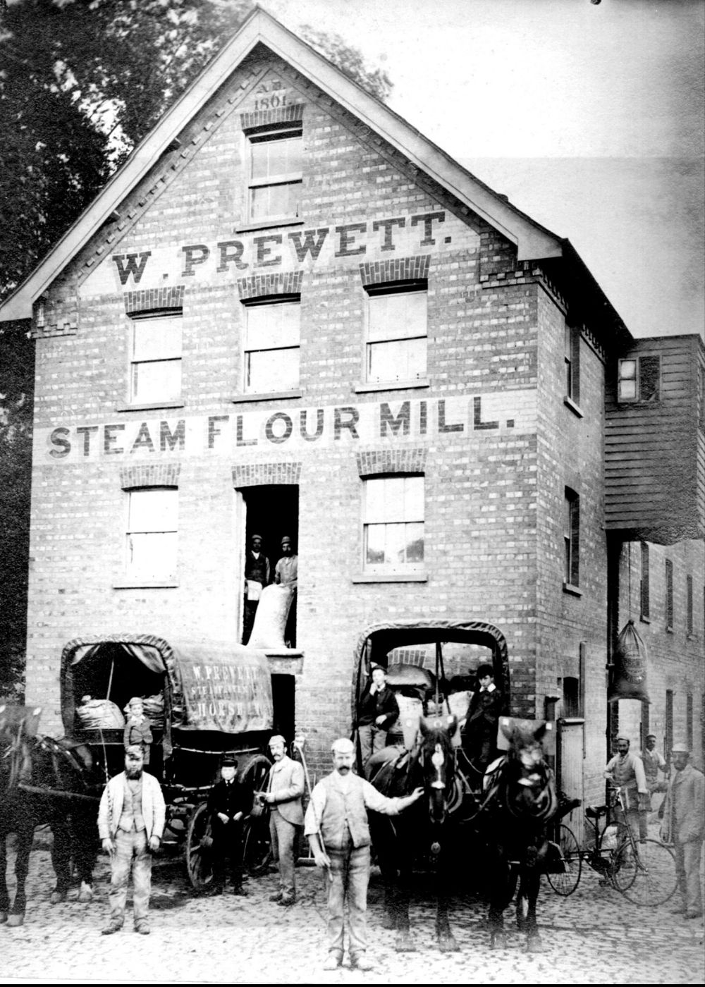 Prewett's Mill, Horsham. Four storey, brick-built structure. A group of men, boys, and horse and carts are at the front of the building.