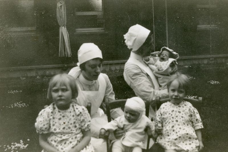 Two nurses pictured in uniform with four young children