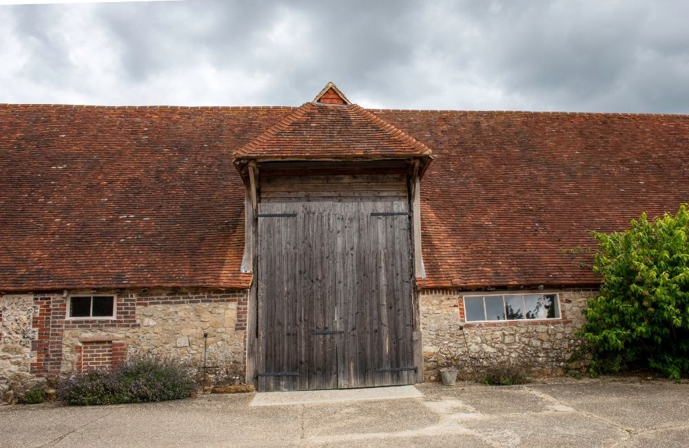 Modern photograph of a large stone barn with a red-tiled roof.
