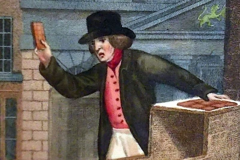 A historic illustration of a man in a top hat and smart jacket selling hot spiced gingerbread in Horsham from a cart