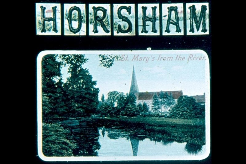 Postcard with Horsham written in capitals. There are 2 images, one of St Mary's Church and one of the Carfax and the bandstand.
