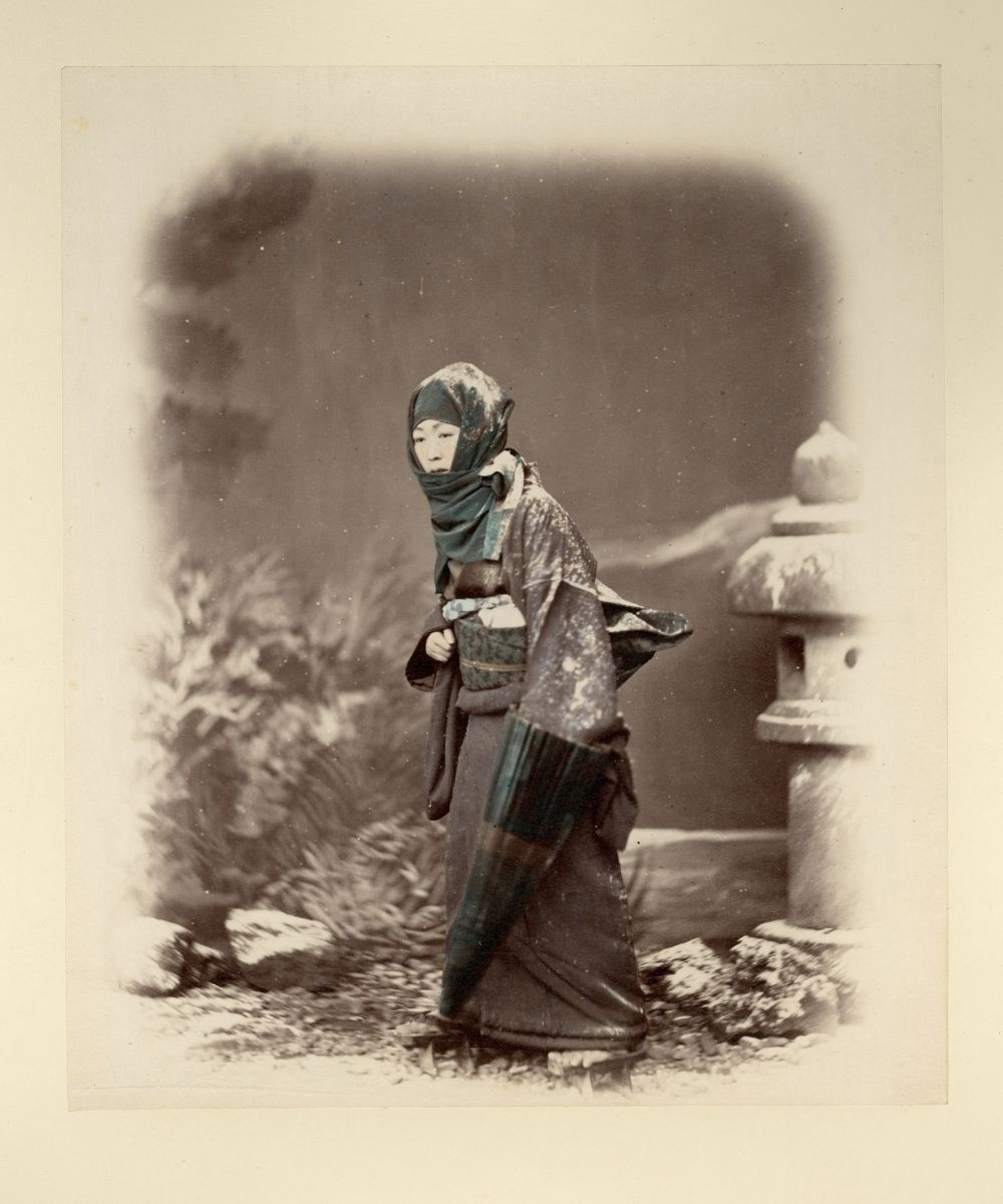 Hand-tinted photograph of a Japanese women walking in the snow