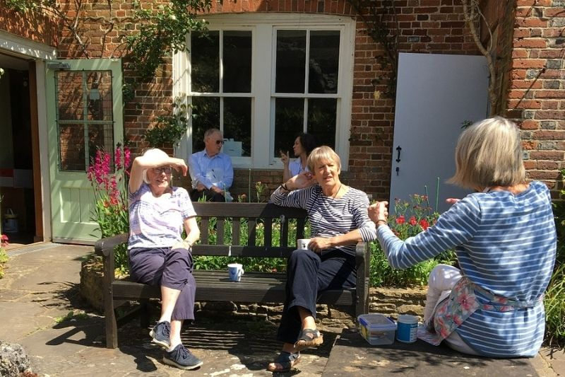 The museum team take a break on benches in the sunny garden