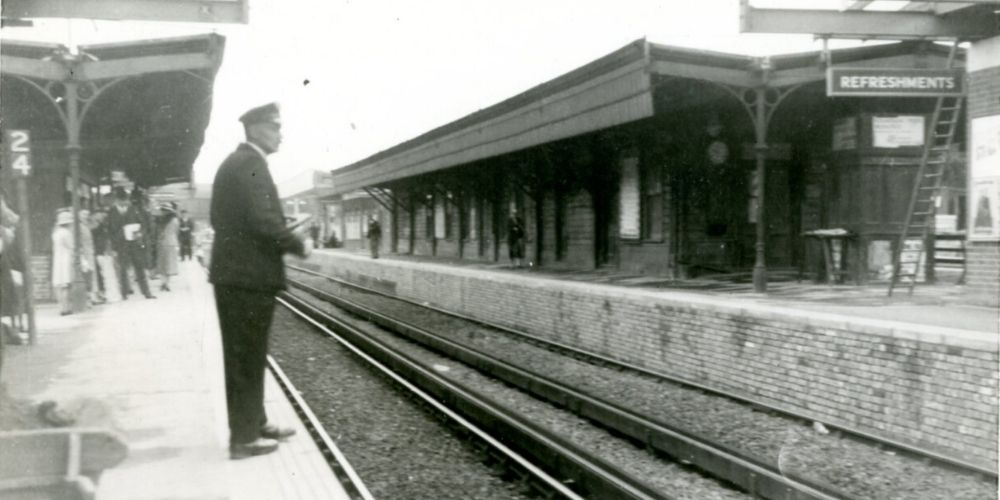 A black and white photo of a Horsham station platform. A guard in uniform stands in the foreground