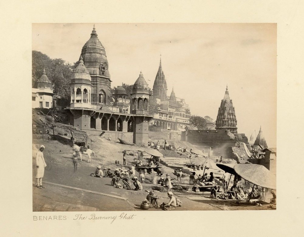 A black and white photo of an Indian waterfront, titled The Burning Ghat