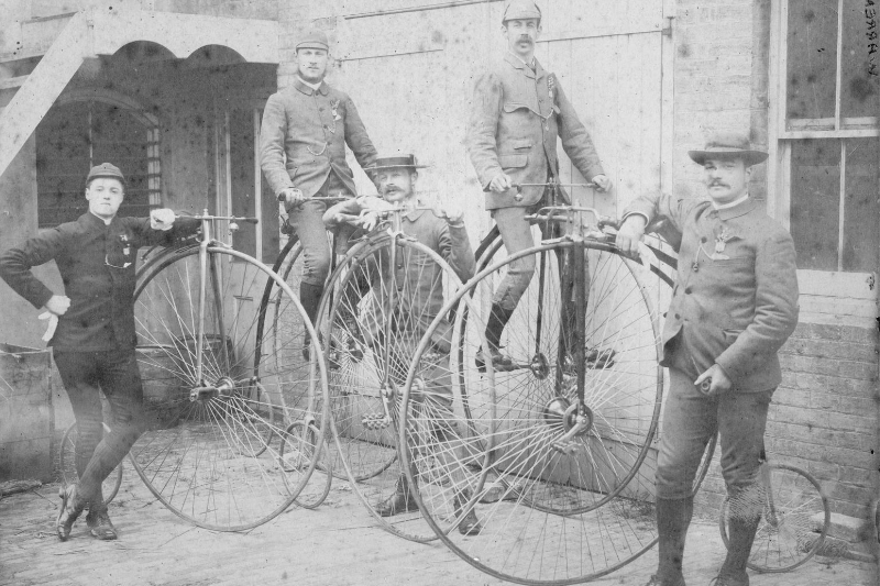 Men standing next to and sitting on pennyfarthings