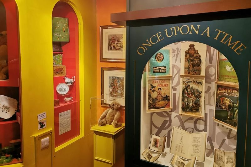 A cabinet with the words Once upon a time contains story books. The yellow and red walls display toys from different eras