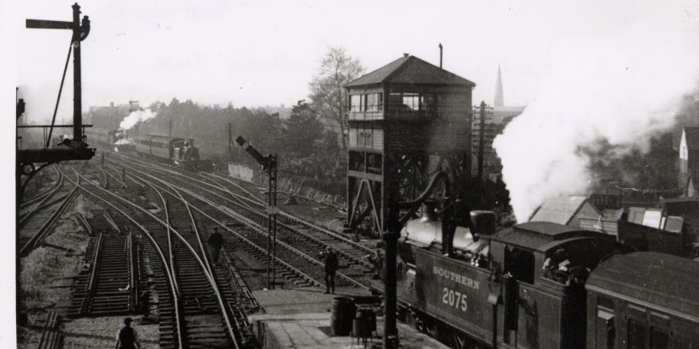 A black and white photo of a Southern Railway train leaving Horsham station