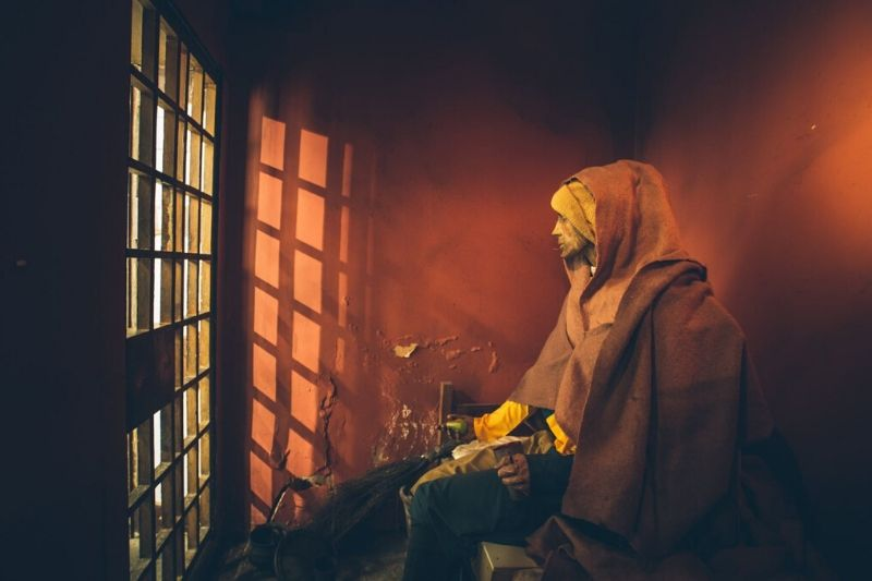A prisoner model sits in the 1775 jail cell