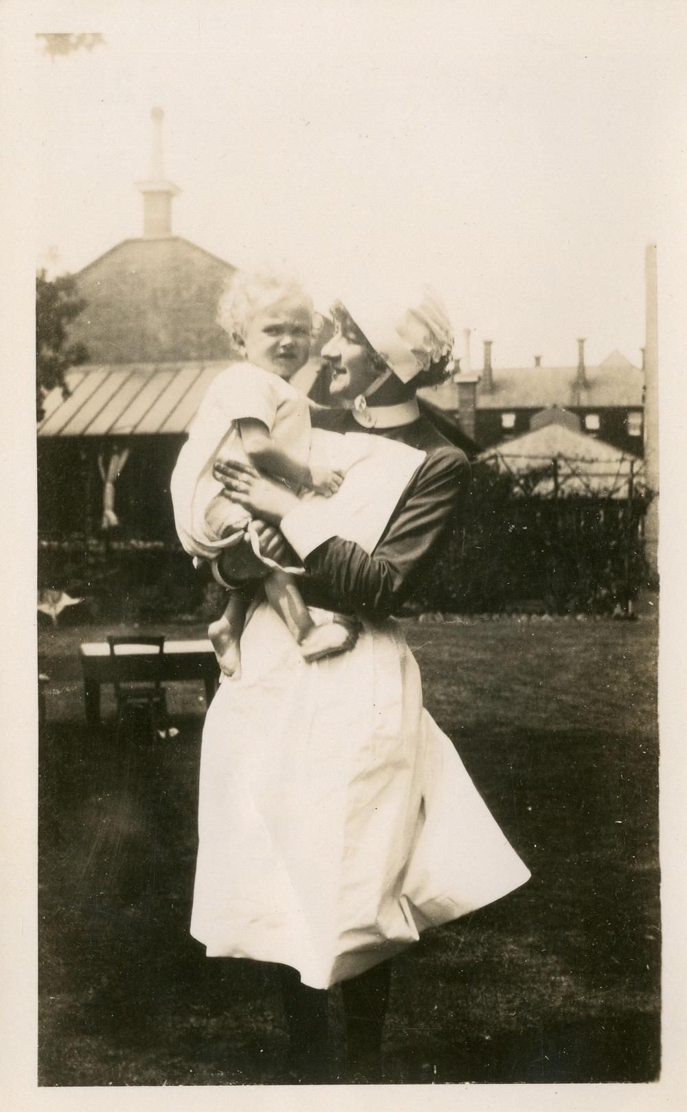 Nurse holding a baby, c. 1920s