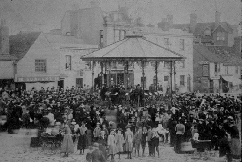 A black and white photo of a crowd gathered at Horsham bandstand