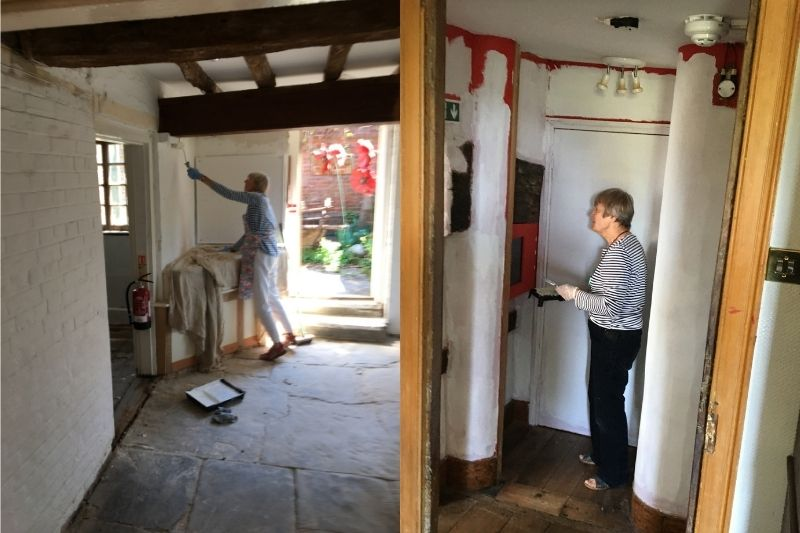 Two volunteers paint a white undercoat over the museum's existing bright colours