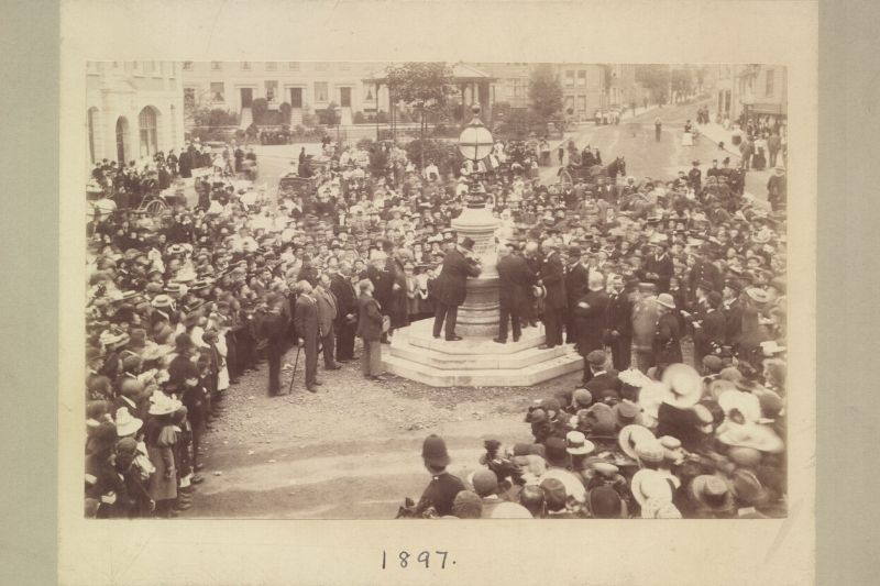 A black and white photo of crowds around Horsham town centre water fountain dated 1897