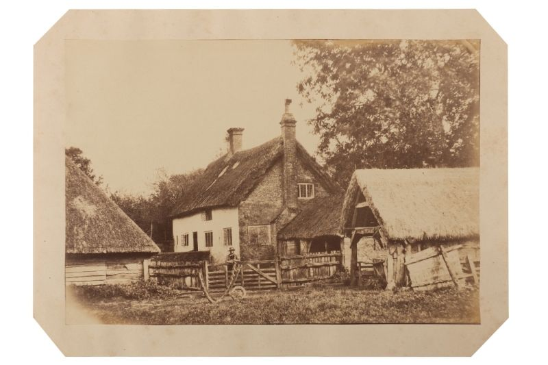Photograph of a farmstead with a man standing by the fence.