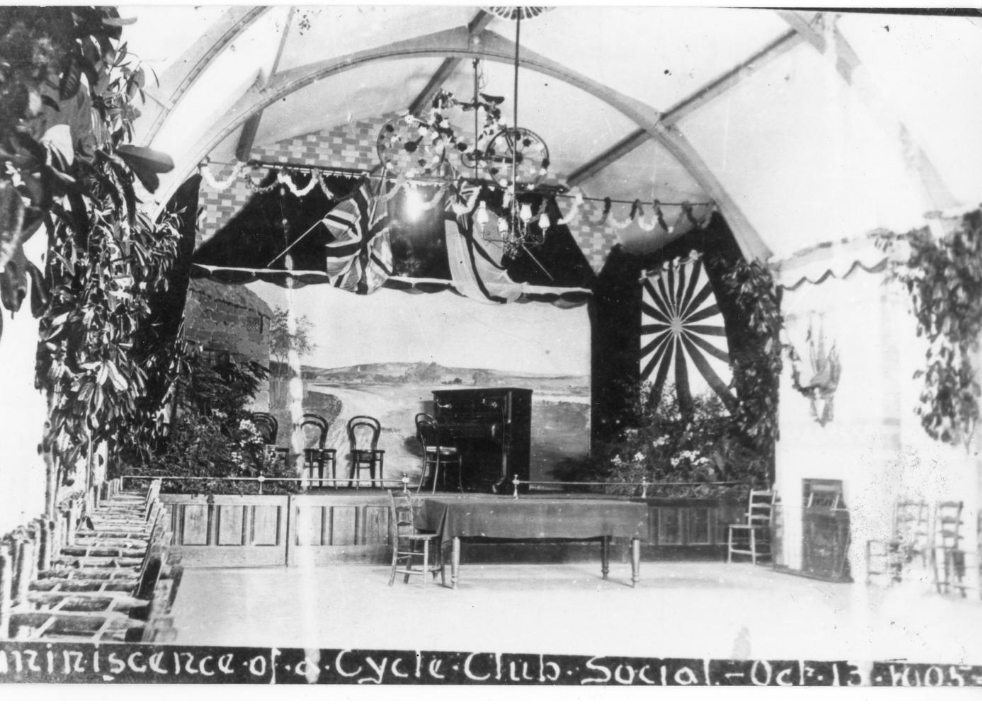 Black and white photo of an old room at a cycle club social